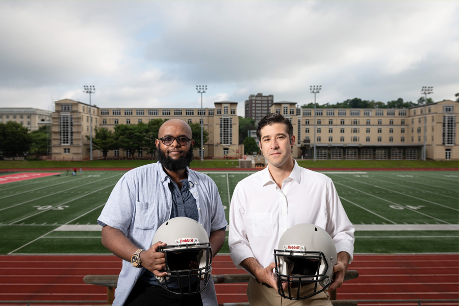 Researchers Brad Mahon and Adnan Hirad stand together holding football helmets.