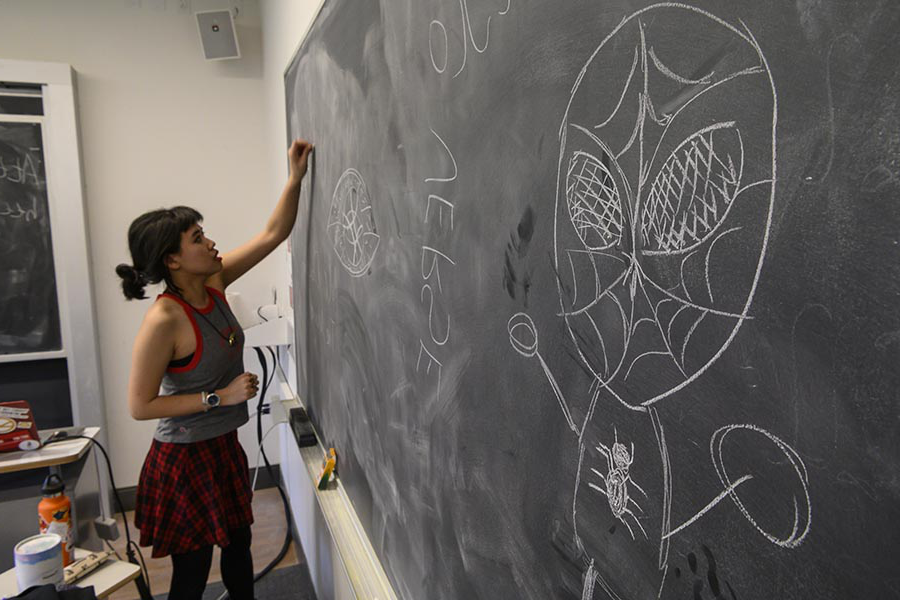 Photo of Izzy Sio drawing on a chalkboard.